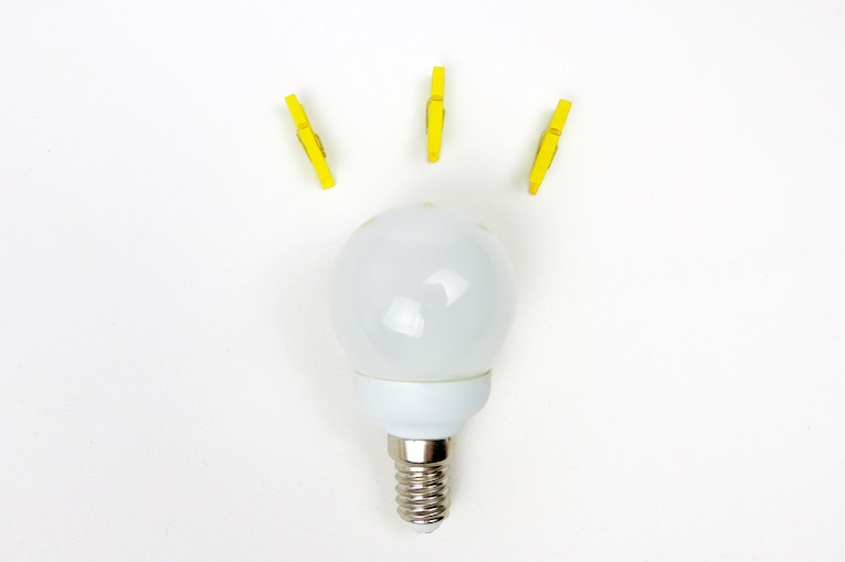 Light bulb on a white background with yellow clothespins
