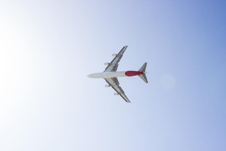 Airplane flying across blue sky