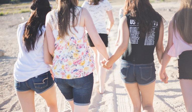 Women walking on the beach holding hands
