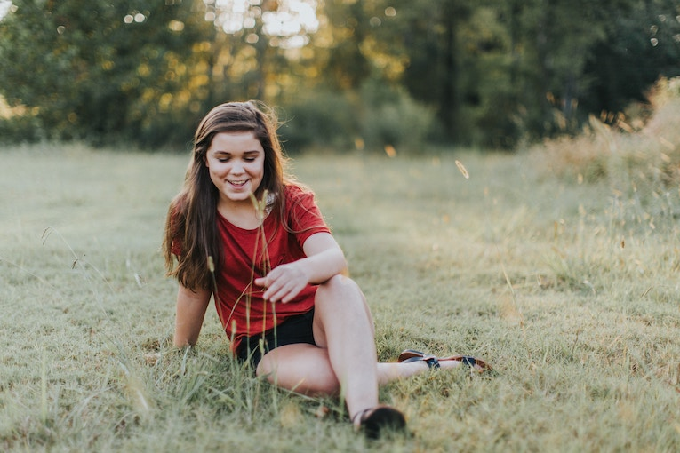 Girl wearing shorts and t-shirt sitting in a field