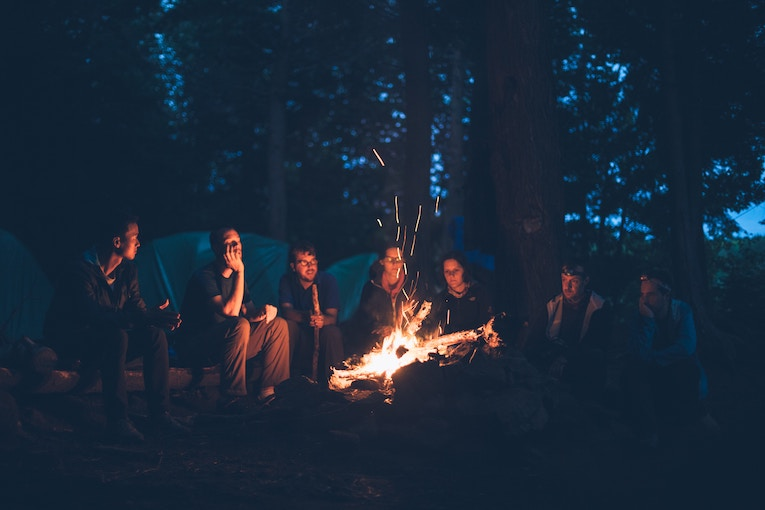 A group of people sitting around a camp fire