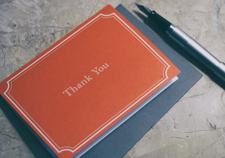 A pile of thank you cards on a table top next to a fountain pen