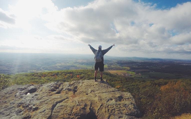 A man standing triumphantly atop a mountain