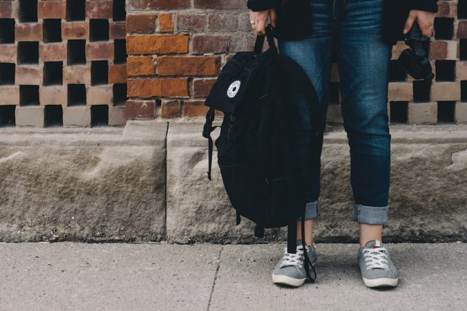 Person standing against a brick wall with a backpack