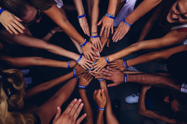 A group of people putting their hands in the middle in unison