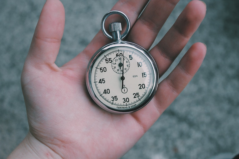 Close up of a hand holding an old pocket watch