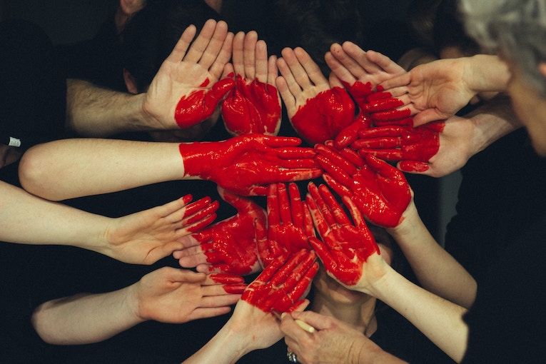 A group of hands in a circle painted with a red heart