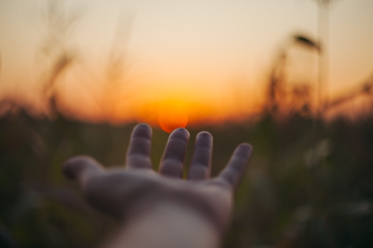 Hand reaching out to the sunset