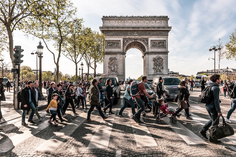 People crossing the street in front of the Arc de Triomphe in Paris