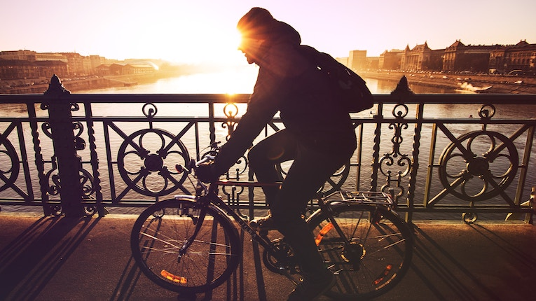 Silhouette of cyclist on a bridge at golden hour