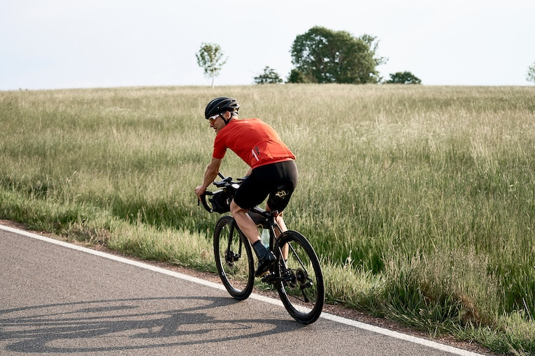 Man riding bike down grassy road