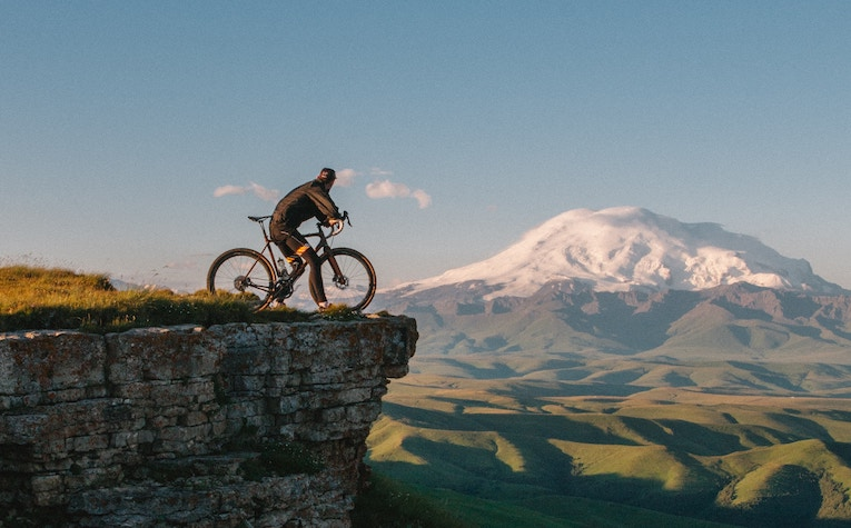 Man parked on a bike overlooking a mountain