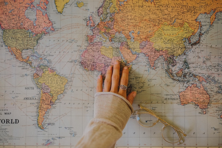 Hand on a colorful world map
