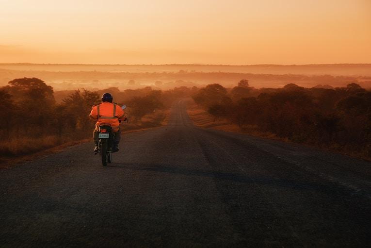 Biker riding down a road in Zambia