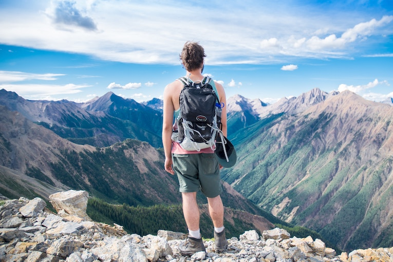 Man standing on a mountain top with a backpack