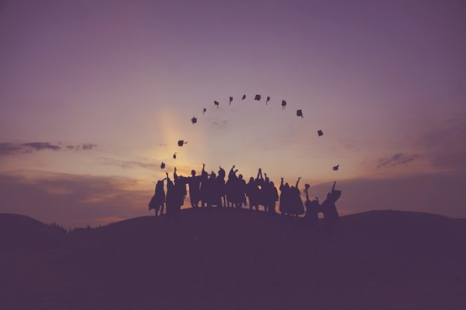 Silhouette of people tossing graduation caps
