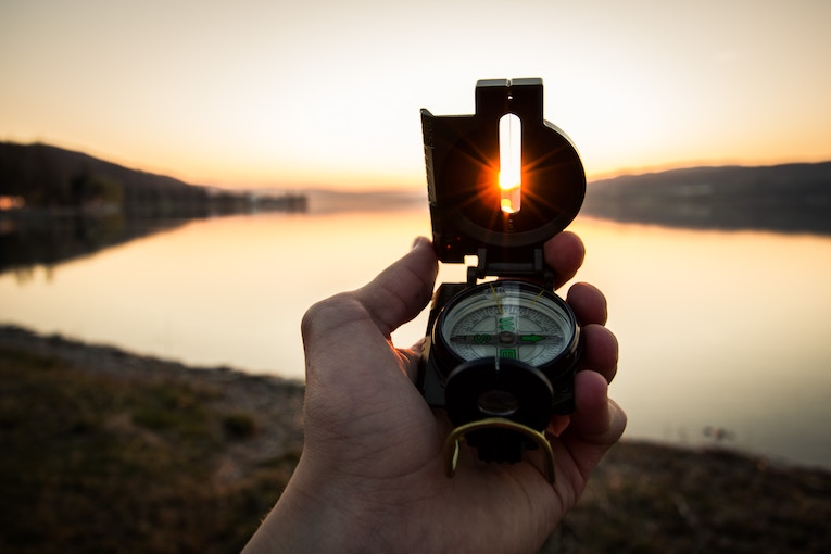 Setting sun behind compass