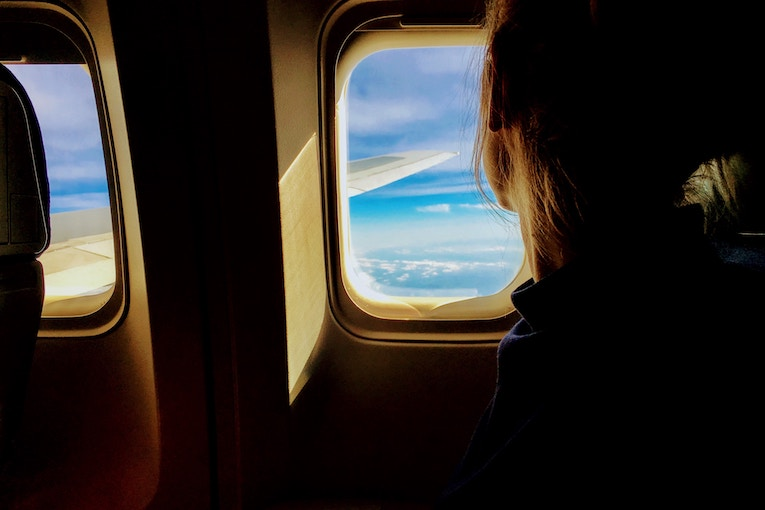 Woman looking out airplane window to bright sky