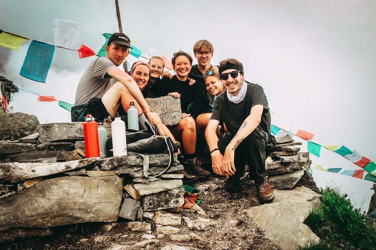 Group of travelers sitting at a mountain summit