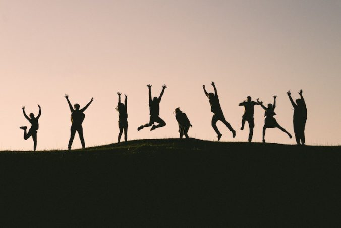 Silhouette of a group jumping on a hill top