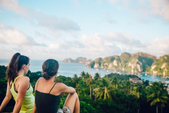 Two women sitting at a scenic overlook in a tropical location