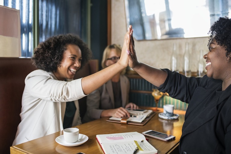 Two women high fiving at a cafe table