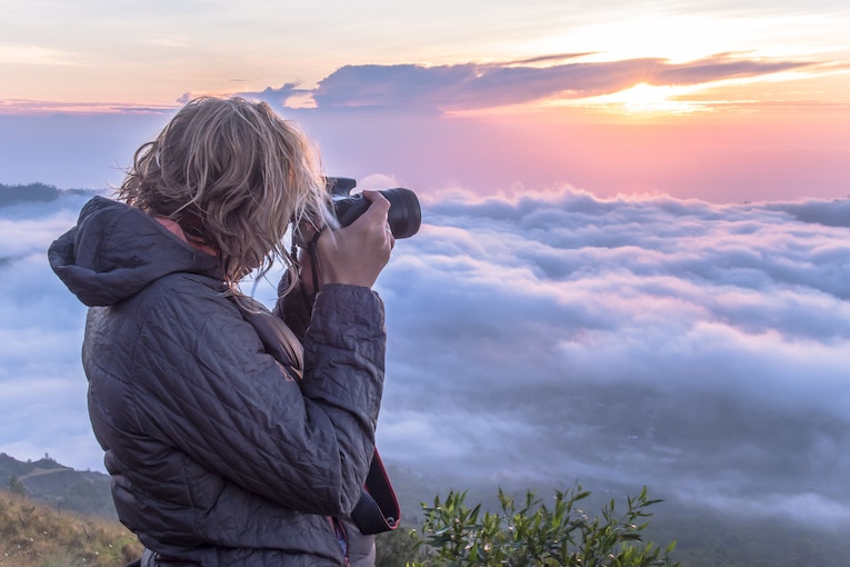 Woman on top of a mountain taking photos