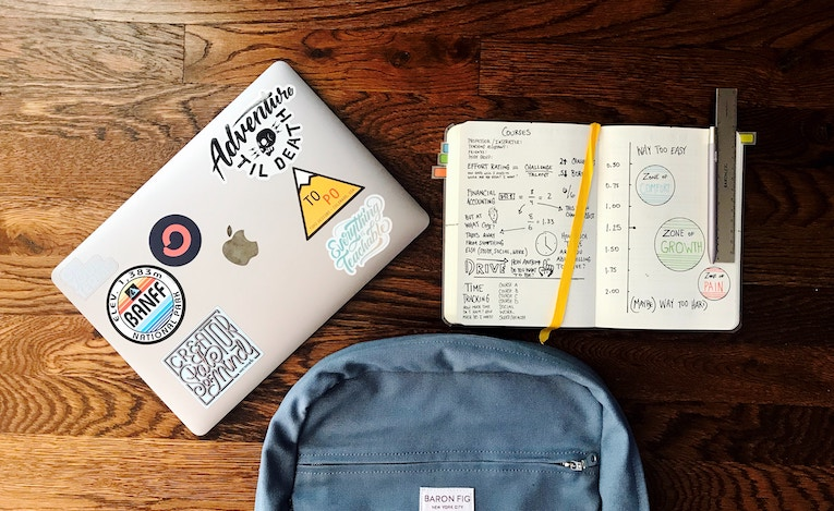 Overhead view of backpack, laptop, and notebook