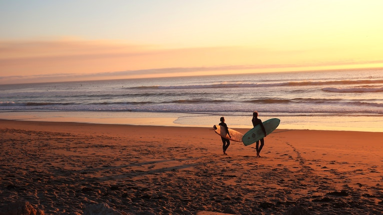 two people wearing wetsuits walking towards ocean with surfboards