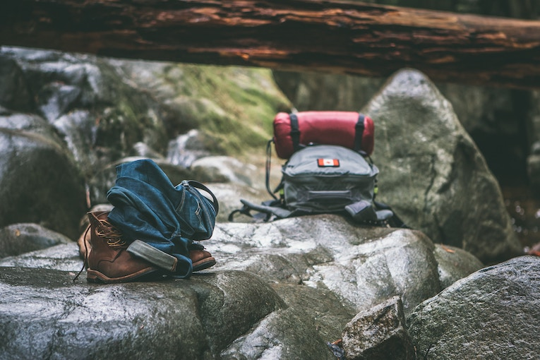 backpacks sitting on wet rocks