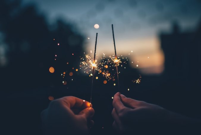 Two burning sparklers at the forefront of sunset