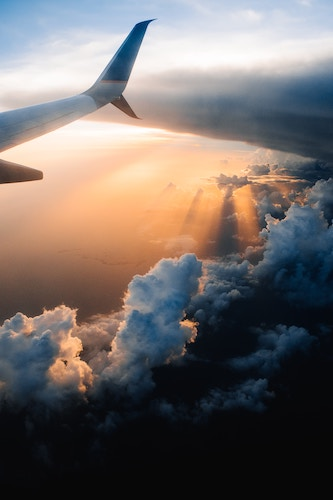 wing of airplane among clouds