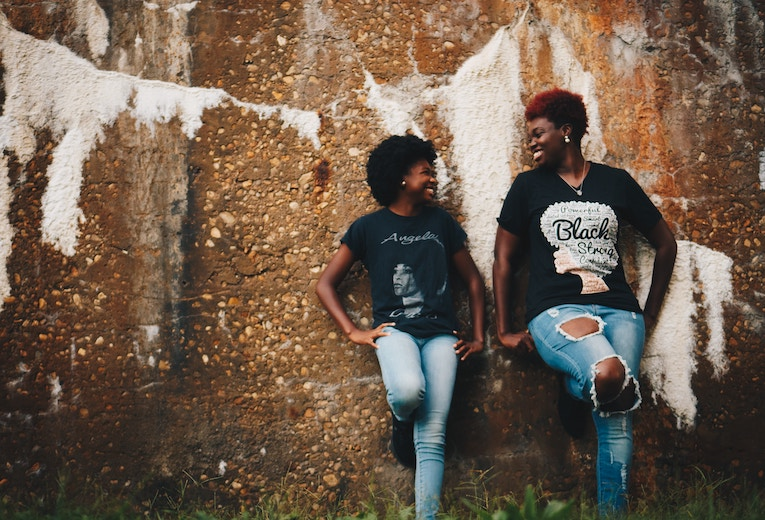 two women standing against wall smiling