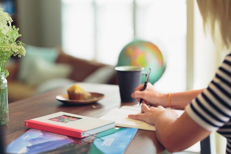 woman writing on tabletop near globe