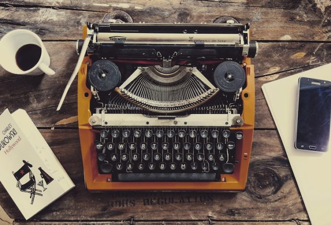 brown typewriter on a wooden desk