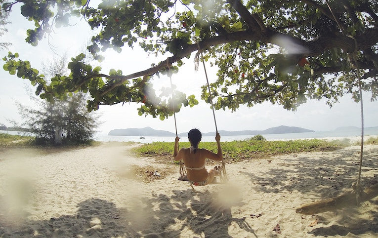 Girl swinging on Thailand beach