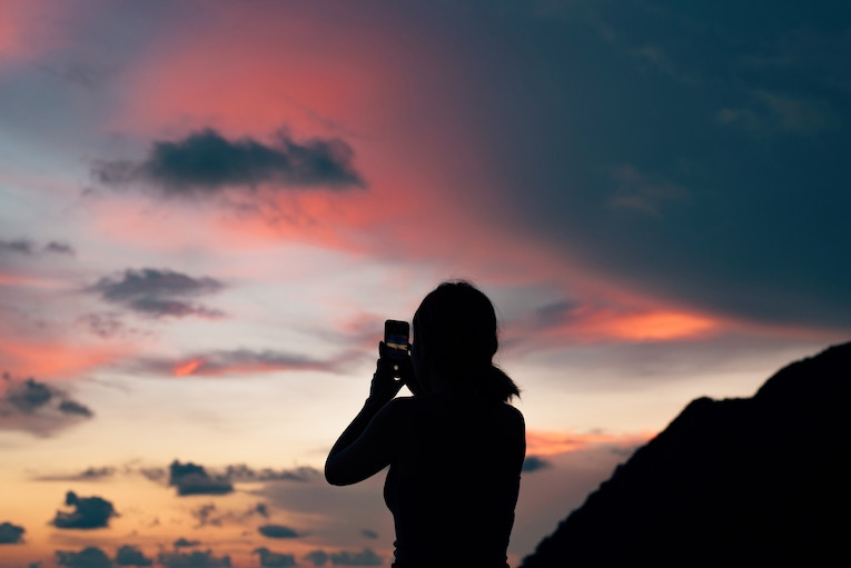 Silhouette of person taking picture of sunset in Thailand