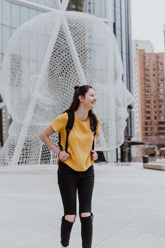 girl with backpack smiling in front of art structure