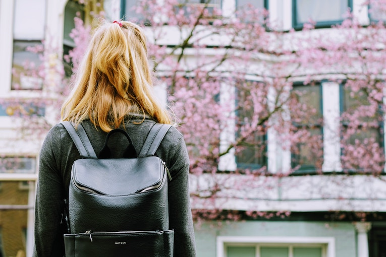 woman with backpack looking at cherry blossoms