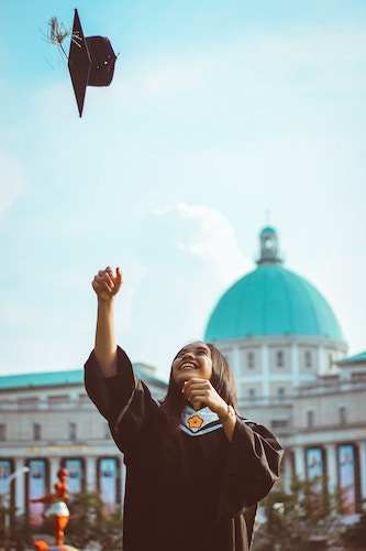 woman throwing graduation cap in the air