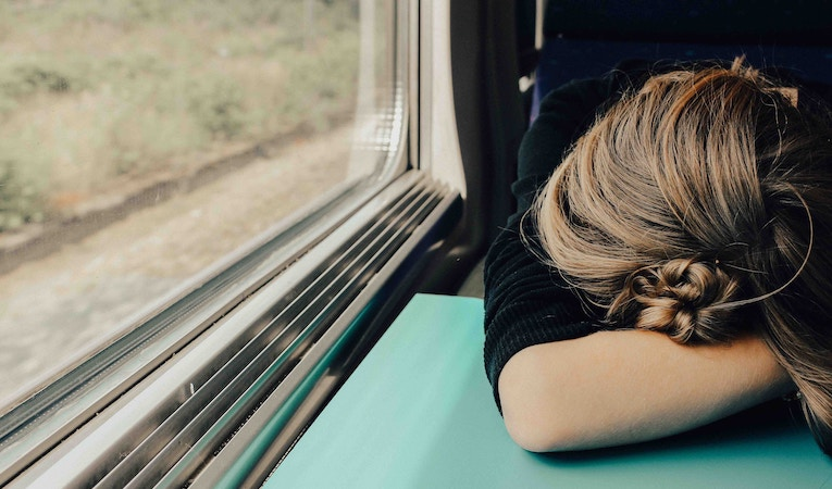 woman with her head down on a train