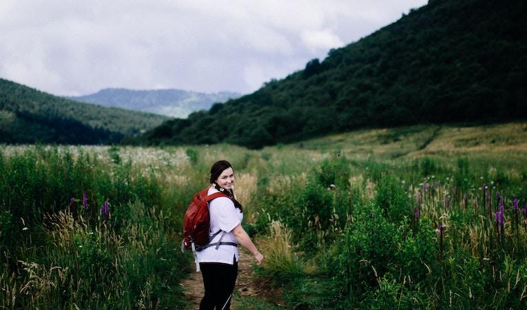 woman wearing backpack in wilderness