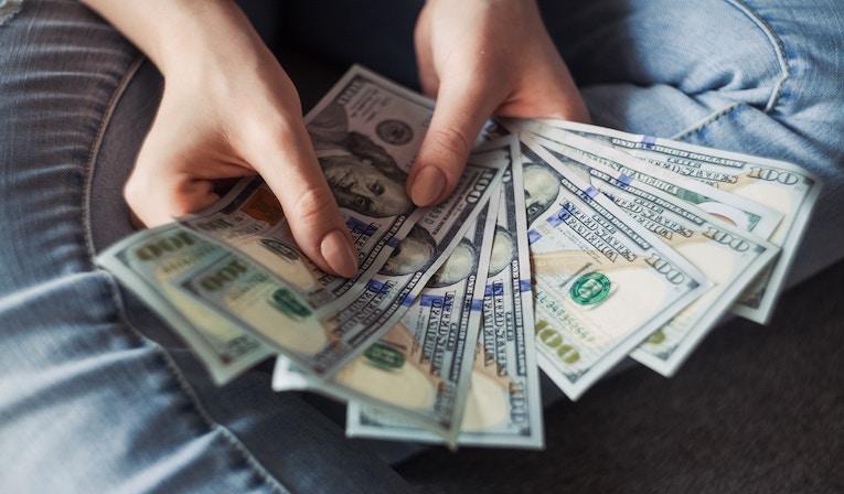 person holding out fan of twenty dollar bills