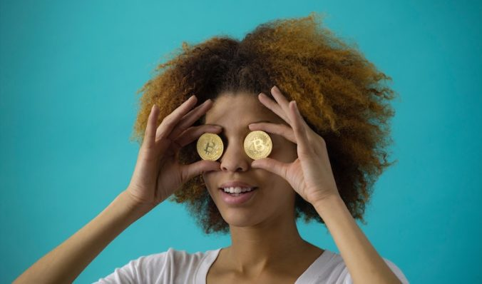 woman holding two gold coins up to her eyes