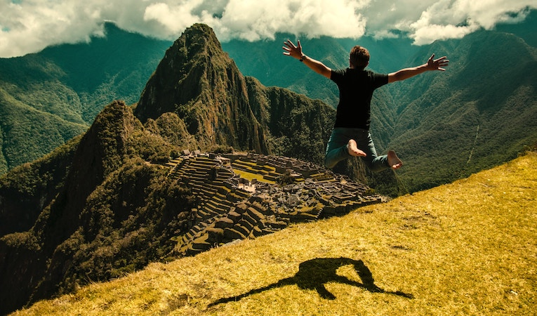man jumping in front of machu picchu