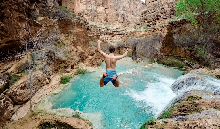 man jumping off cliff into water