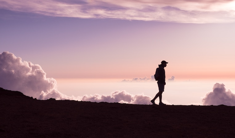 silhouette of person walking in front of clouds and purple sky