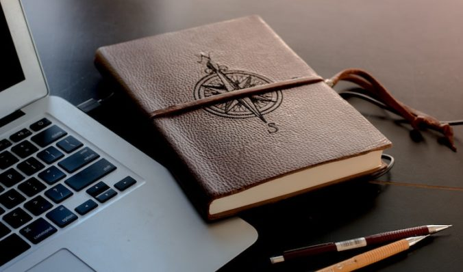 journal embossed with compass next to computer