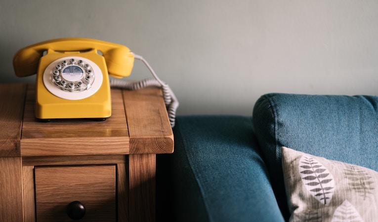 rotary phone next to sofa