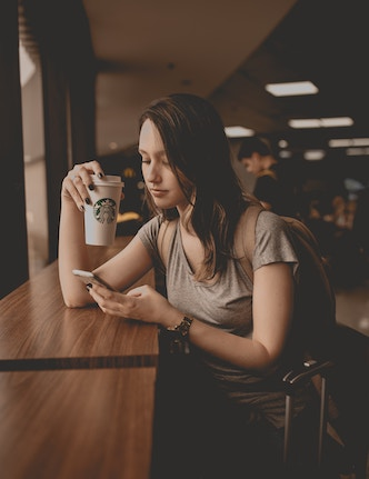 person holding coffee cup and cell phone